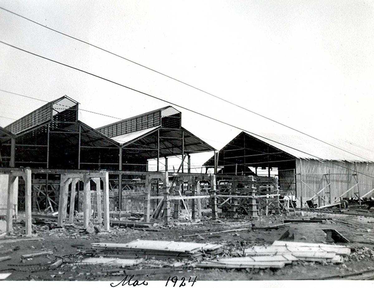 """""""xx/05-1924"""" Nitriden. Bygninger for steking av elektrodekull. Bærende konstruksjoner for skinnegang, """"høybanen"""", i forgrunnen. Taubanewire. Kai anlegget til høyre."""