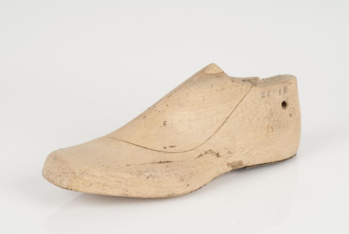 En tremodell i to deler; lest og opplest/overlest (kile), med påført tekst. Venstrefot i skostørrelse 41 med 9 cm i vidde. Hælstykket er av metall.