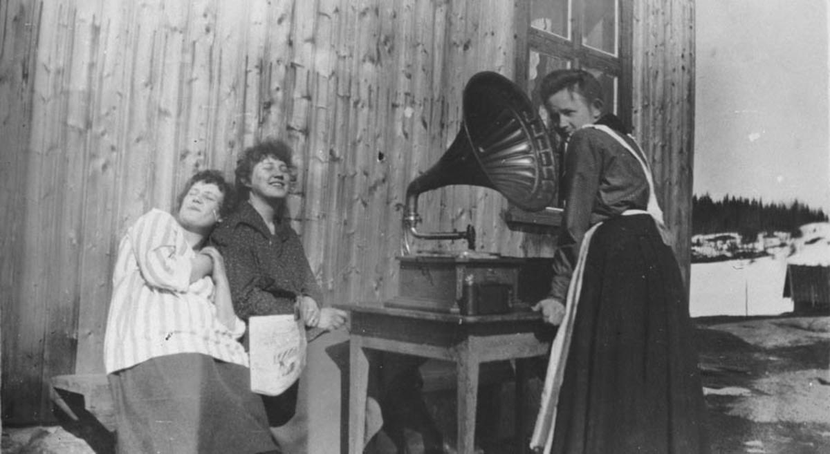 "3 kvinner koser seg med gammel ""trakt"" grammafon."