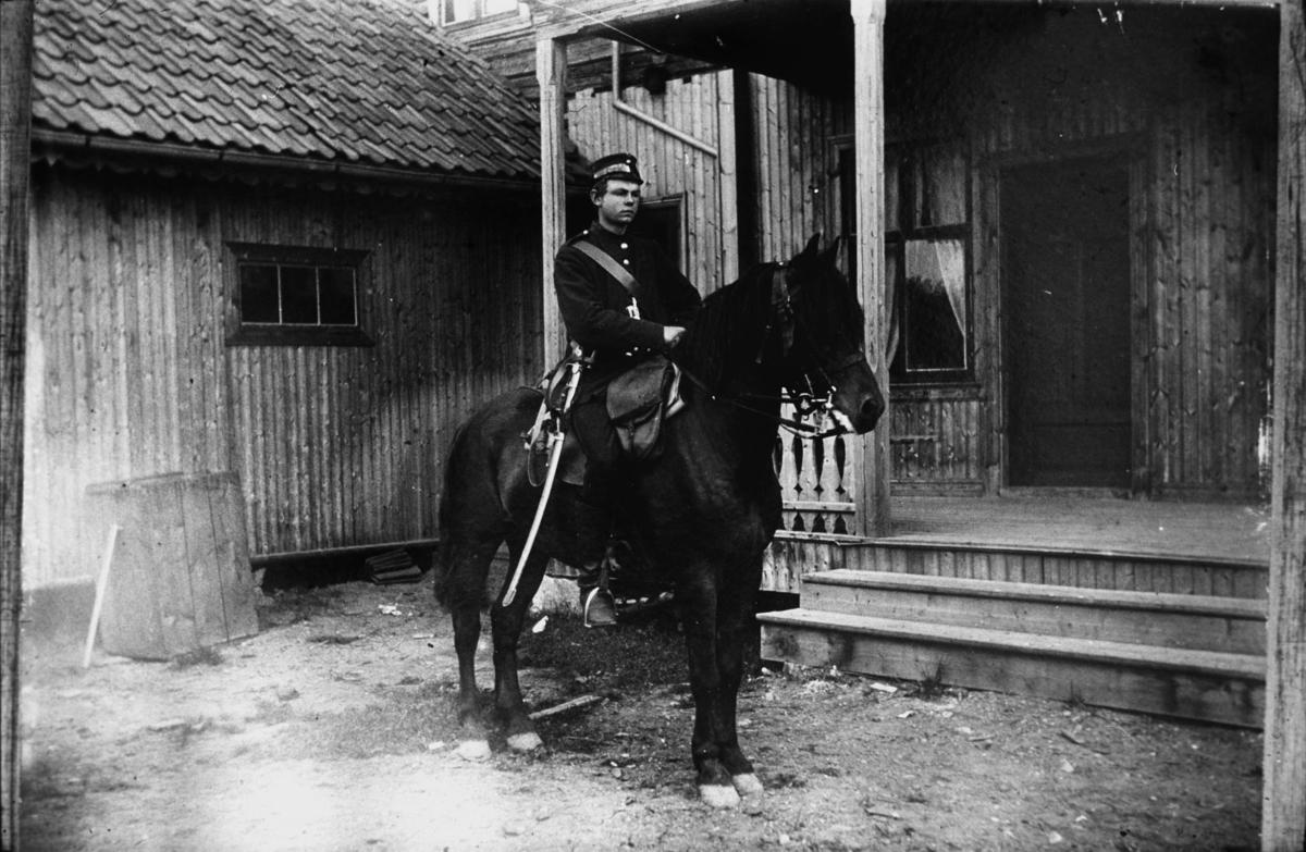 Soldat til hest oppstilt inne i et gårdsrom.