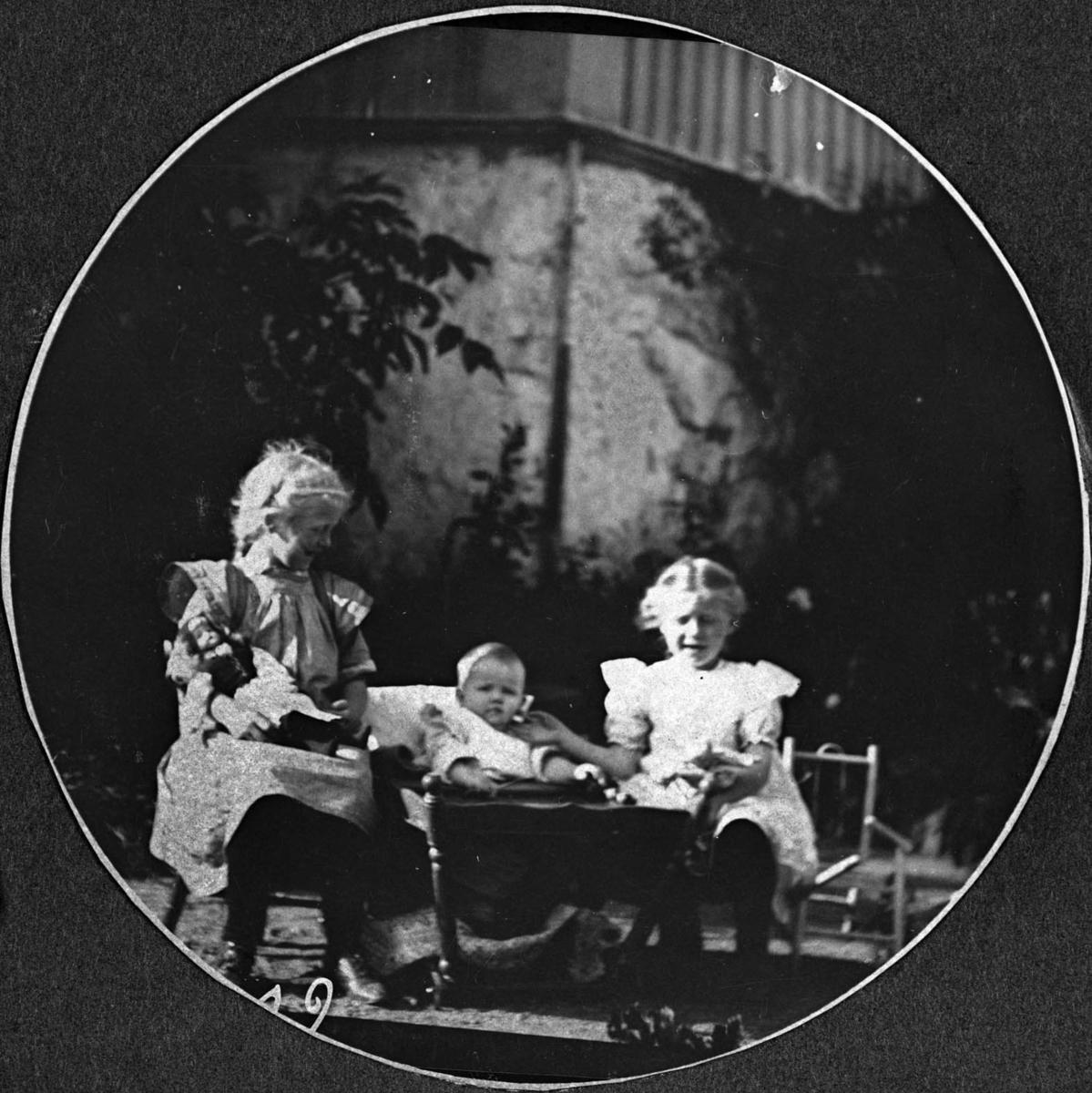 To store og et mindre barn fotografert ute, vogn, barnmøbler, drakt, pike
