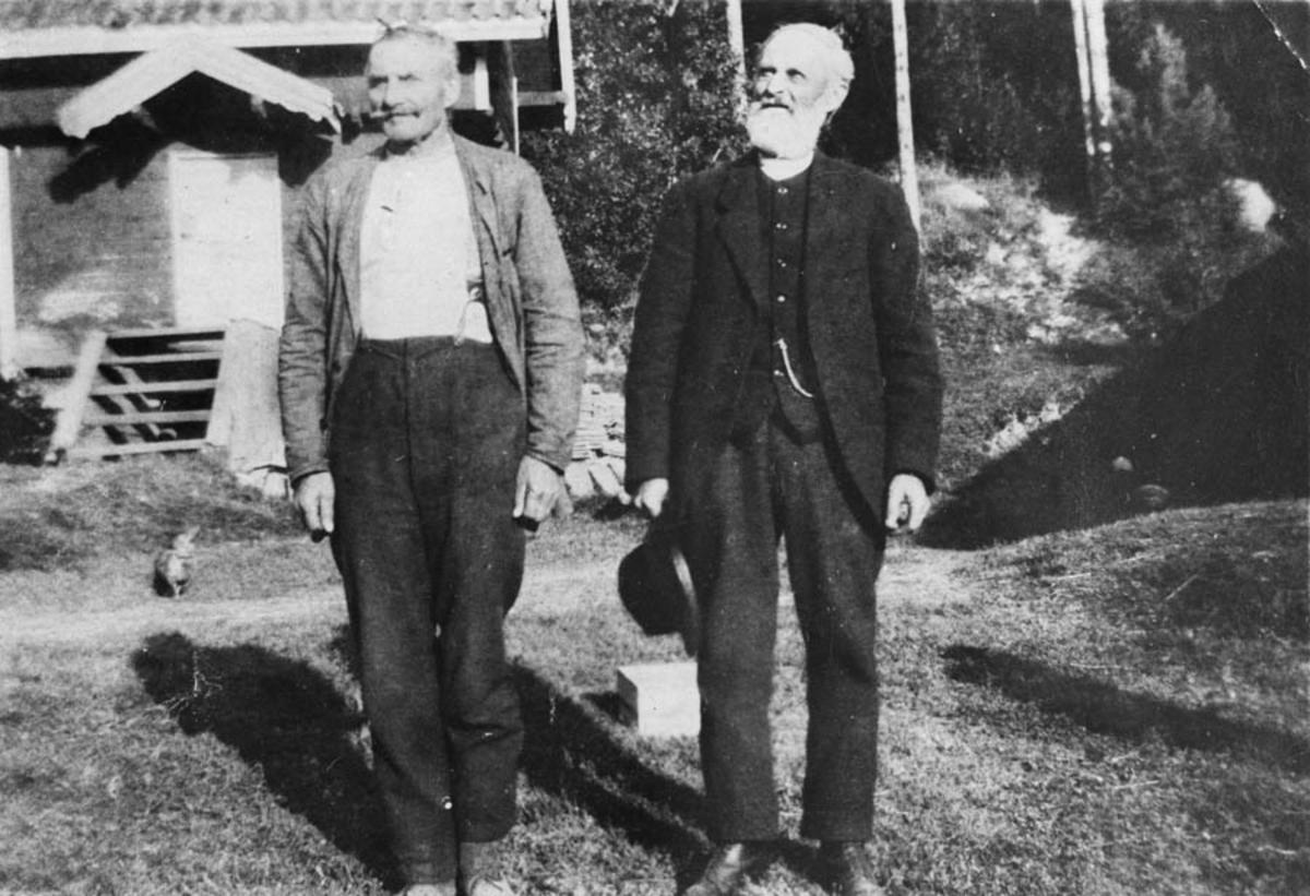 To eldre menn foran et hus.