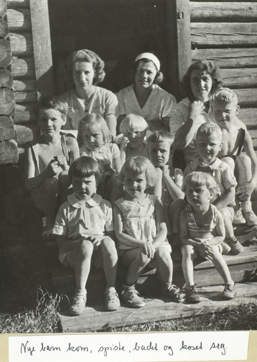 Tolv personer, tre voksne damer og ni barn sittende på trapp til tømmerhus