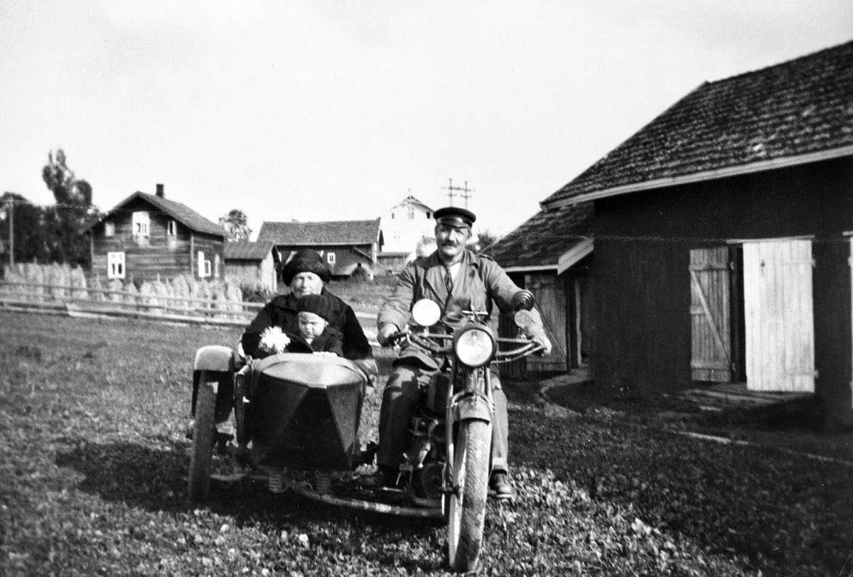 Motorsykkel med sidevogn. Mann på sykkelen med kvinne og barn i sidevognen. Oppstilt ved et uthus, i bakgrunnen et hus og korn på staur. Ukjent sted