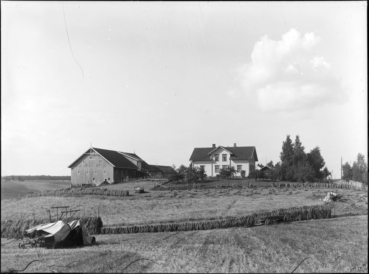 Ukjent gård i innhøstinga, flere vogner og landbruksredskaper på jordene.