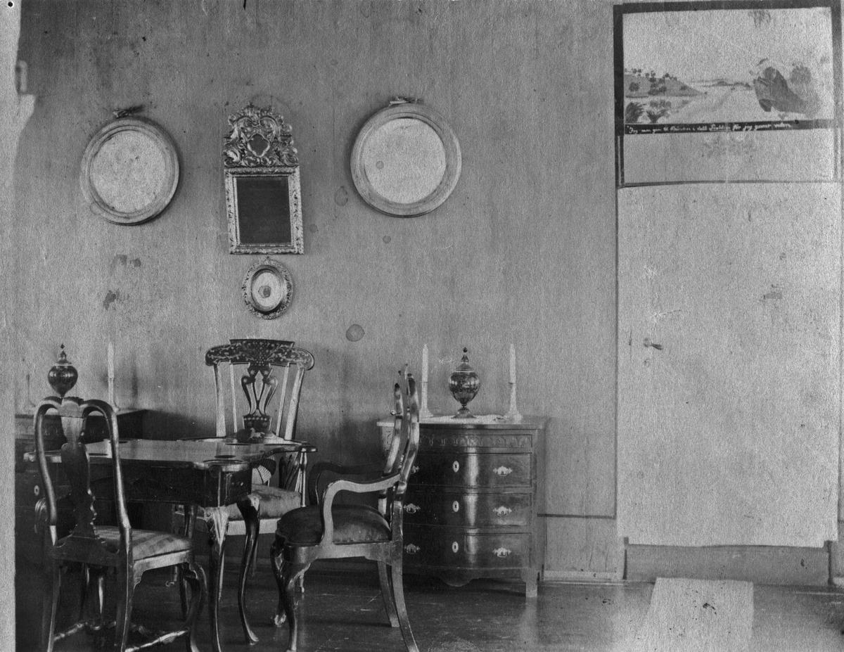 """Interiør fra Badet. """"De ser paa væggen over døren Wergelands maleri: Presten som gaar i vandet""""."""