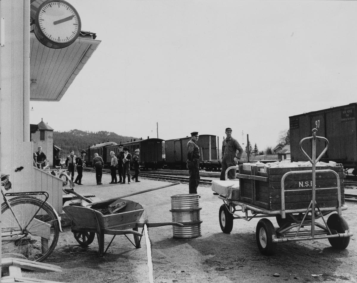 Reisende, gods og jernbaneansatte venter på toget på Bjørkelangen stasjon.