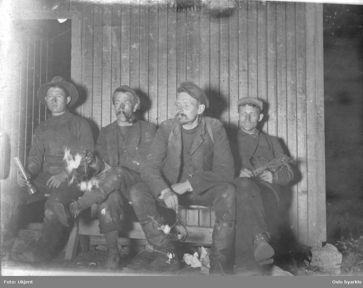 Fire arbeidere eller tømmerfløtere tar en pause i koia