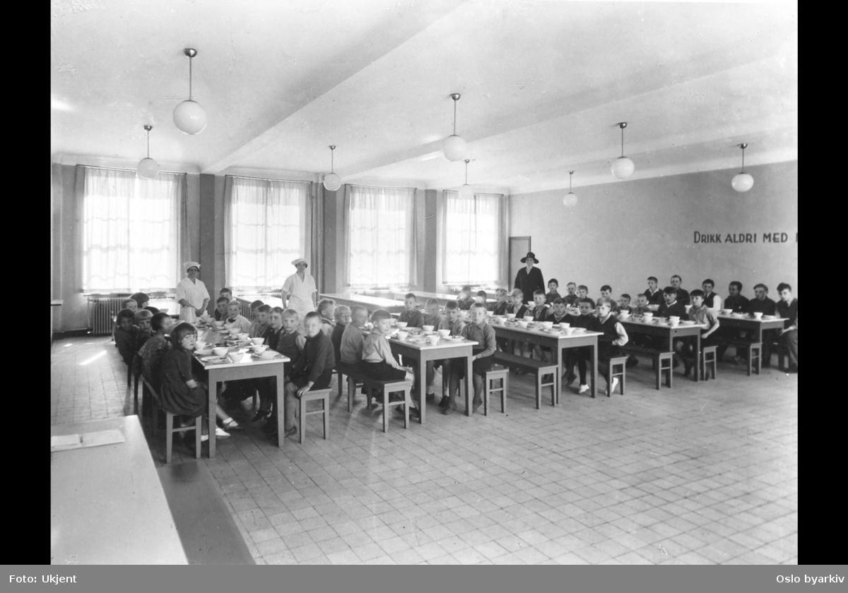 """Barn som spiser skolefrokost. Lærerinner som passer på. Påskrift på veggen: """"Drikk aldri med (mat i munnen)"""". Møllergatens skoles utvidelse, 1933 (albumtittel) (Møllergata skole). Kommentar fra bruker: Jeg er født i 1938, men bildet med møbler og tekst på veggen er velkjent. Etter at tyskerne som hadde okkupert M?llergata skole hadde forlatt landet. kunne vi igjen ta skolen i bruk. Det inkluderte Oslofrokosten, som ble inntatt nettopp i denne salen. Jeg misforsto teksten på veggen slik at jeg spiste alle smørbrødene (med brunost) før jeg drakk noe som helst. Jeg har vondt for å tro at tyskerne lot denne salen forbli urørt, og tror bildet stammer fra siste halvdel av 40-årene."""