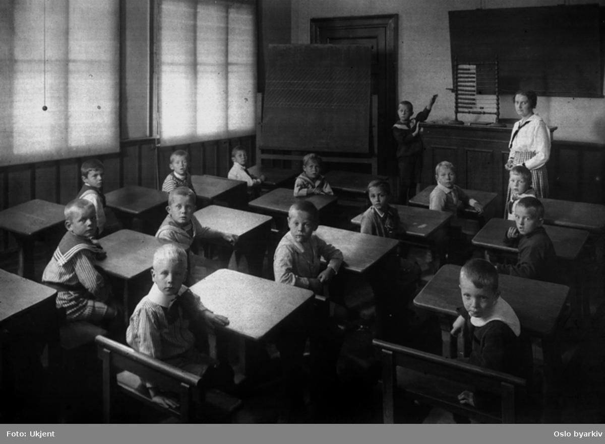Gutteklasse med deres lærerinne. Matematikkundervisning med kuleramme. Forberedelsesskolen. Skolepulter. Klassebilde.