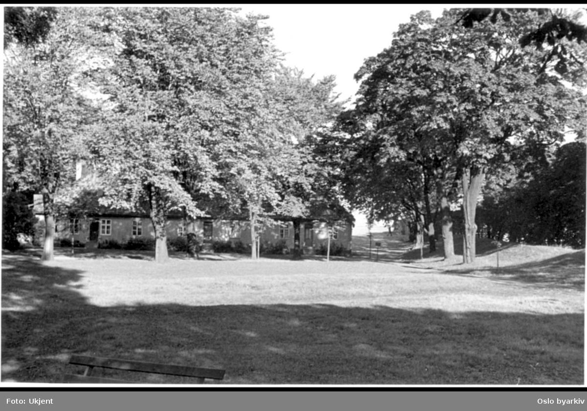 Festningsområdet (Lensherrens hage) på Prins Carls bastion og nordover mot hovedvakten og borgporten mot øst og Kongens gate. Barakkene (1747) ses midt i bildet. Munkedammen ble gjennskapt i 1960. Gardist marserer fra porten til hovedvakthuset i bakgrunnen.