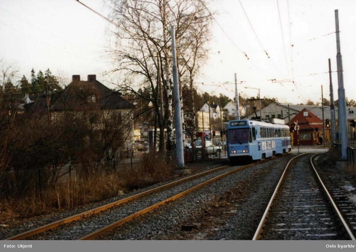 Leddtrikk nummer 264 på linje 9, Ekebergbanen, på vei mot Ullevål hageby. Holtet stoppested og senter i bakgrunnen.