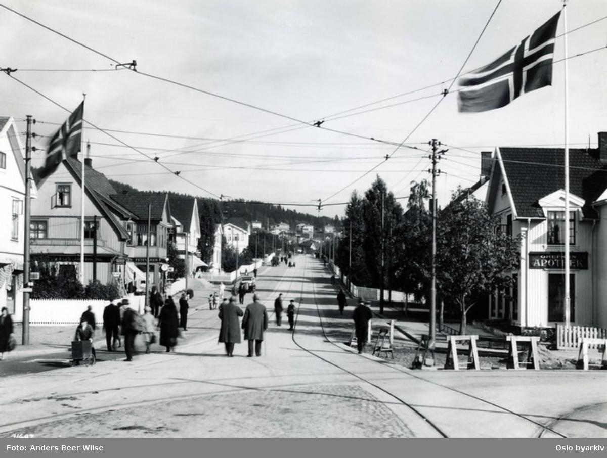 Storokrysset på en flaggdag, norske flagg heist i flaggstenger.Trikkesporet som går gjennom boligområdet opp Grefsenveien. Wilse foto 41697.