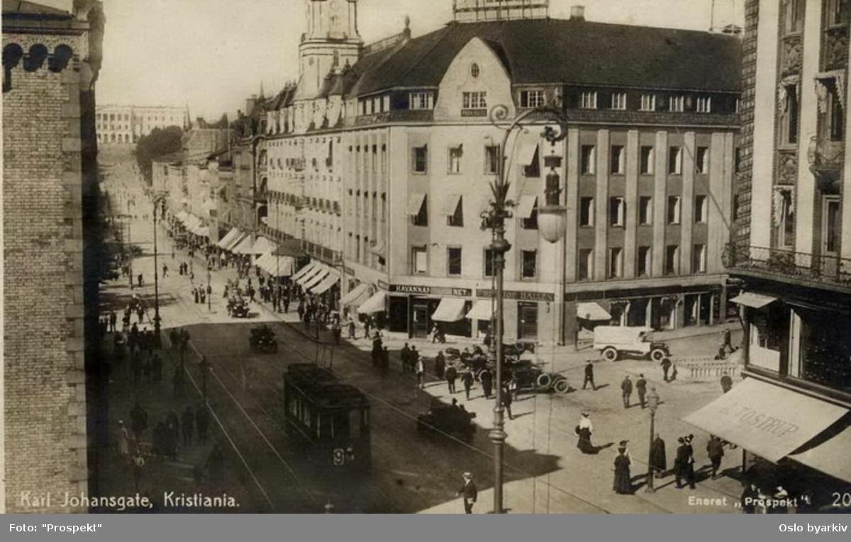 Grønntrikk motorvogn 94 type SS linje 9 fra Rodeløkka over Stortorvet, her i Karl Johans gate ved Stortings plass og Brambanigården. Gatebilde, gatelykt, folkeliv. Postkort. Bilde tatt en gang mellom 1915-1920.