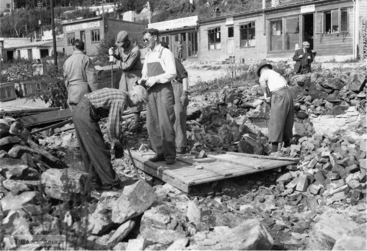 """Tomterydding i Molde sentrum, med forretningsbrakker i bakgrunnen..Rydningsarbeid i Molde sentrum våren 1942. .(Se """"Romsdal Sogelag 1988"""" side 8)"""