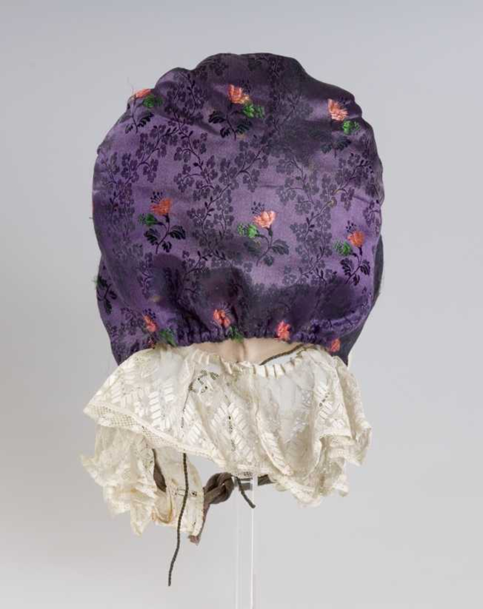 Rynkelue i fiolett silke med innvevde fiolette blomstermønster i rødt, grønt, svart. Tyllblonde i hvitt bomull, fôr av lin, knyteband av mønstret bomull.