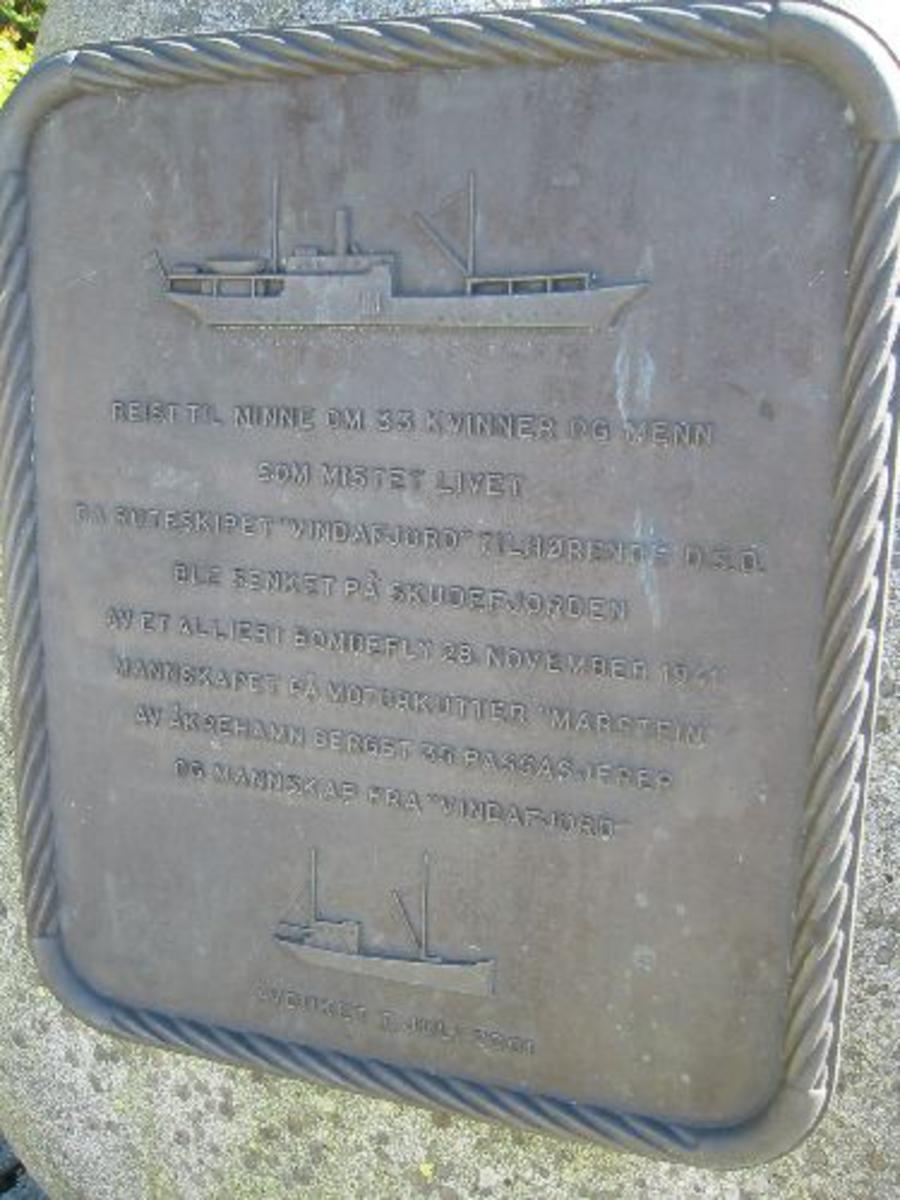 Minnelund med hellelagt område og oppsatte benk og en bronseplate med bilde av båten og navneliste oppsatt på en stein. Platen er h 0,65 x b 0,55. Steinen den er satt på er rund og 1,40 h 1,00 b 0,50 d