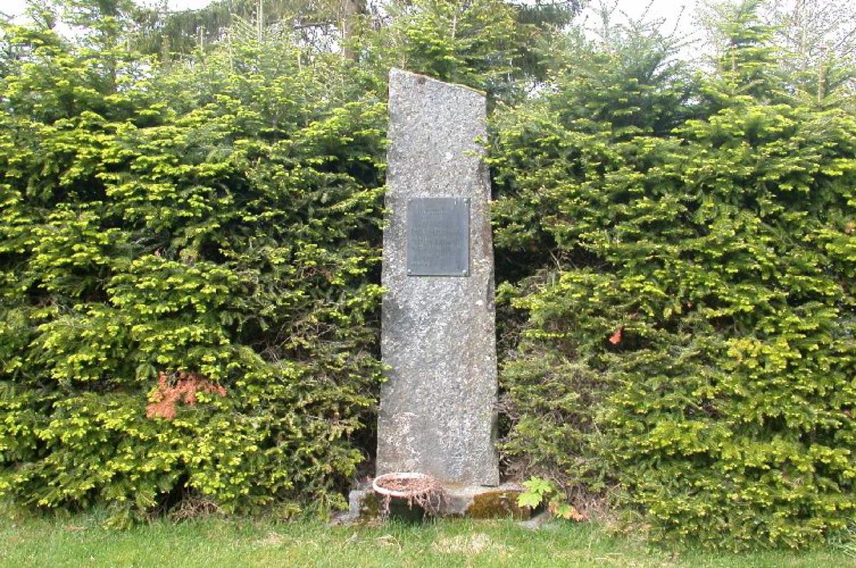 Hogd stein ca 2,5 m høg med minneplate i kopper.