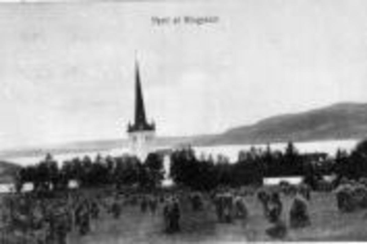 Landskap rundt Ringsaker kirke mot Mjøsa. Kornsnes til tørk i forgrunnen.