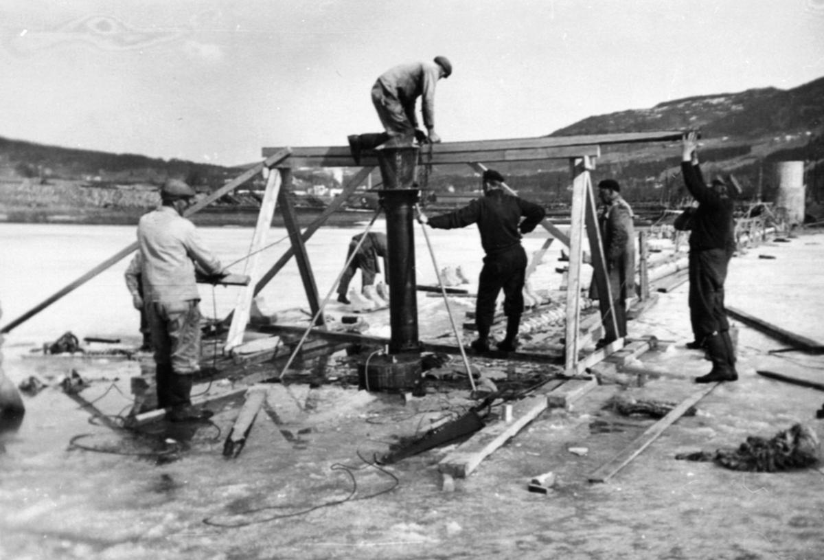 Bygging av vanninntak, pumpestasjon, inntaksil settes på plass, Hedmark Tørrmelk, Tine, Brumunddal. 8 menn arbeider.