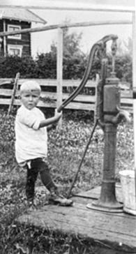 OLINE J. HOLTER VED VANNPUMPE, GAMMEL BRØNN, VINDHOL STORE