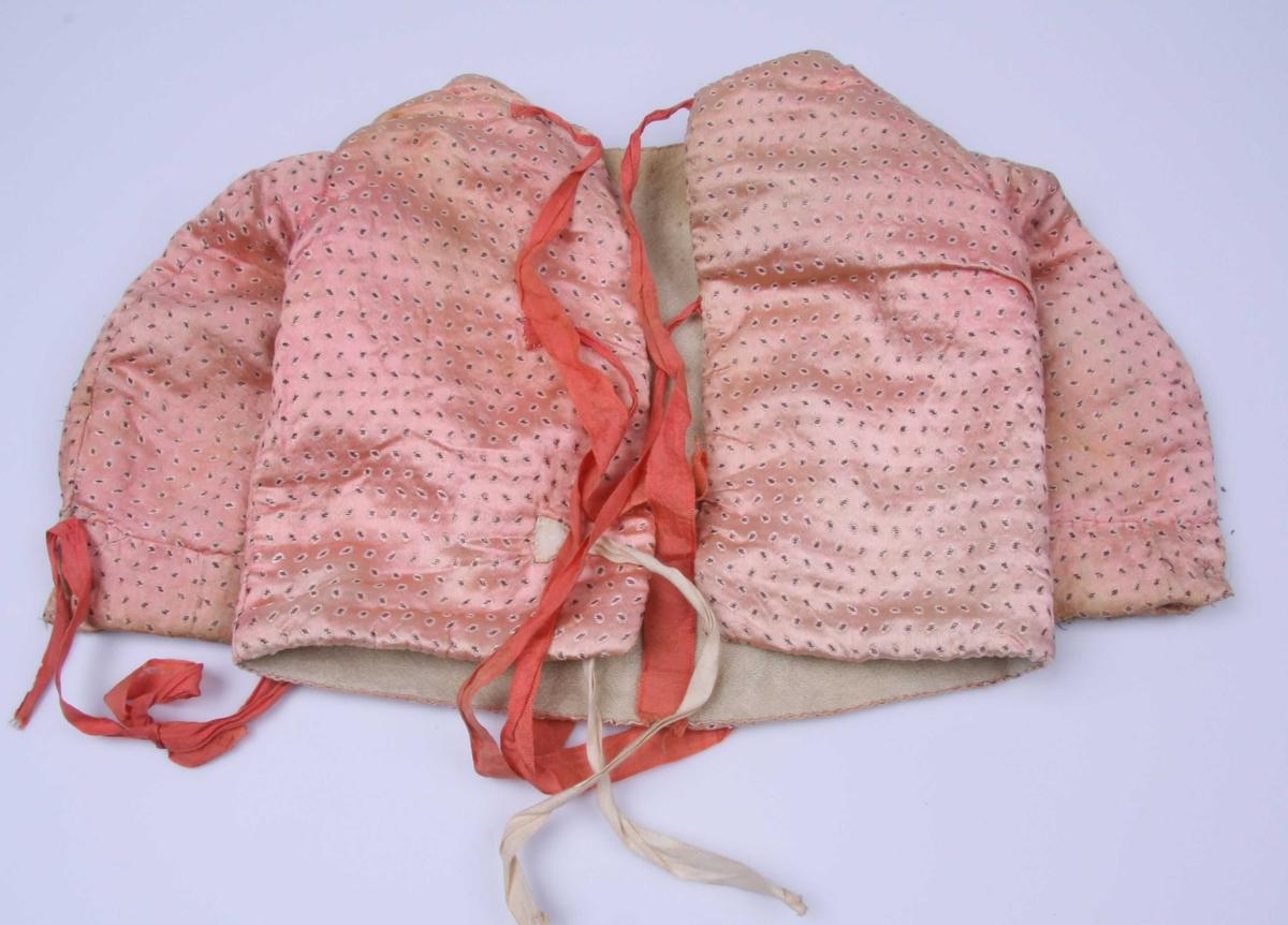 Av rosa atlask med lysere rosa paletter med mørkebrun kjerne. Ermene har linning nederst med knapphull og knapp, mangler. Et rødlig-rosa silkebånd er sydd fast overfor splitten for å knytes rundt håndleddet, mangler på det ene ermet. Samme slags knytebånd i ryggen. Ett av dem er erstattet med et bendelbånd. Fôr av hvit vadmel.