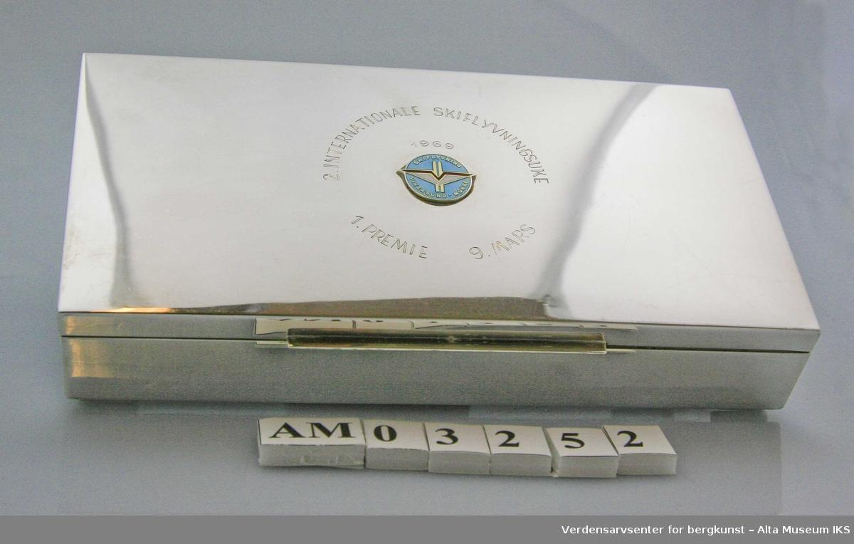 Form: Rektangulært skrin m/hengslet lokk, foret m/trefinér. Emaljert emblem i rødt, hvitt og blått og ski med vinger + Skiflyvning Vikersund - Norge Bunnen i skrinet er av finer.
