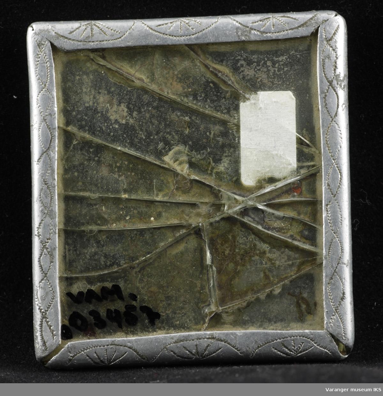 Speil i tinnramme. Gravert/siselert dekor i front og påskrift bak.