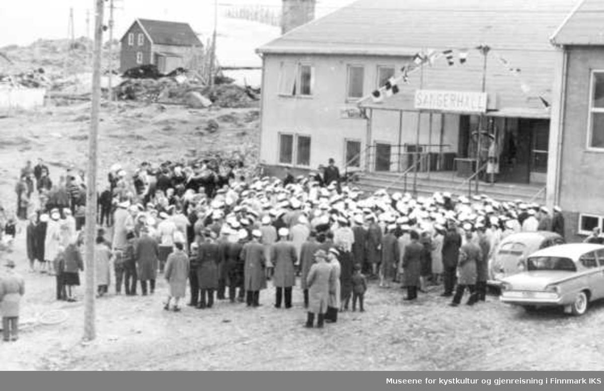Samfunnshuset som sangerhall. Hornmusikken spiller. Medlemmer av arrangementkomiteen står på trappen. Damekorstevne i Berlevåg, 1962