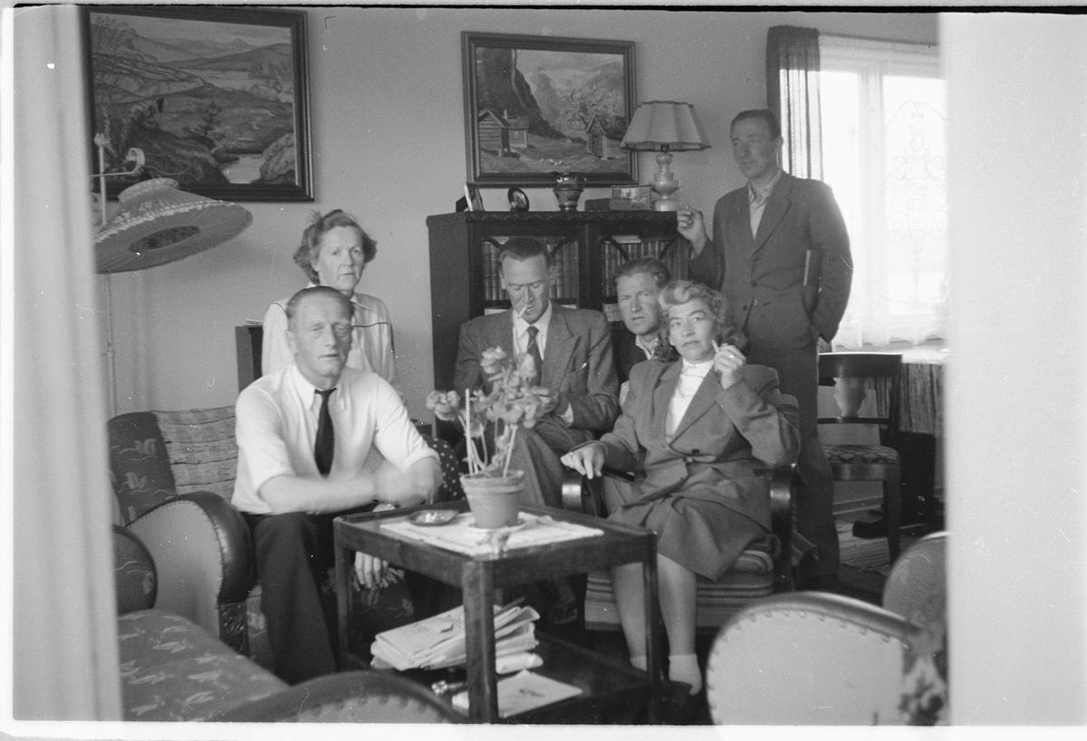 Interiør, stue. En gruppe mennesker samlet rundt stuebordet. Fra venstre; Paul Pettersen, Martha (f. Prestkværn) hans kone, Einar Prestkværn, Håkon Prestkværn, ukjent dame (Einars 2. kone). Mann i bakgrunnen ukjent.