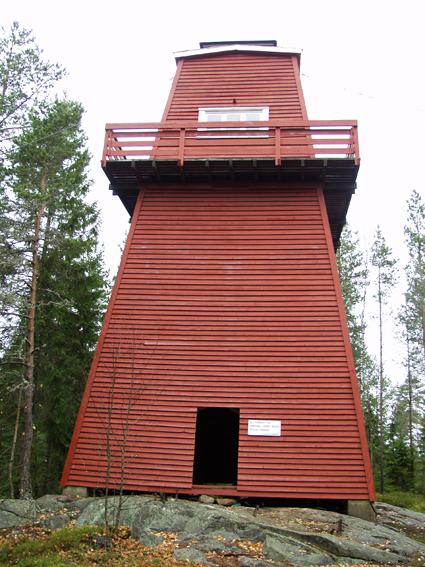 Skogbrannvakttårnet på Hauknesfjellet i Rømskog i Østfold.  Fotografiet ble tatt i forbindelse med oppmålingsarbeid da Norsk Skogmuseum begynte å arbeide med planer om å bygge en kopi av tårnet på museumsområdet i Elverum.   Tårnet på Hauknesfjellet ligger 335 meter over havet med fin utsikt over vide skogtrakter.  Det første tårnet på dette stedet ble reist i 1909, det neste i 1928.  Det avbildete tårnet skal etter informasjon i forsikringsselskapet Skogbrands arkiver å dømme være bygd i 1953.  Det er reist på et skjellett av stolper (rundtømmer) som er kledd med rødmalt horisontal bordkledning (vestlandspanel).  I den øvre delen av tårnet er det innredet to rom - et oppholdsrom med utvendig balkong på fire sider og et overliggende utkikksrom under en takhatt med vinduer i alle himmelretninger.  Dette fotografiet viser tårnets fasade mot sør, der inngangen til tårnfoten med trappeoppgang er plassert.