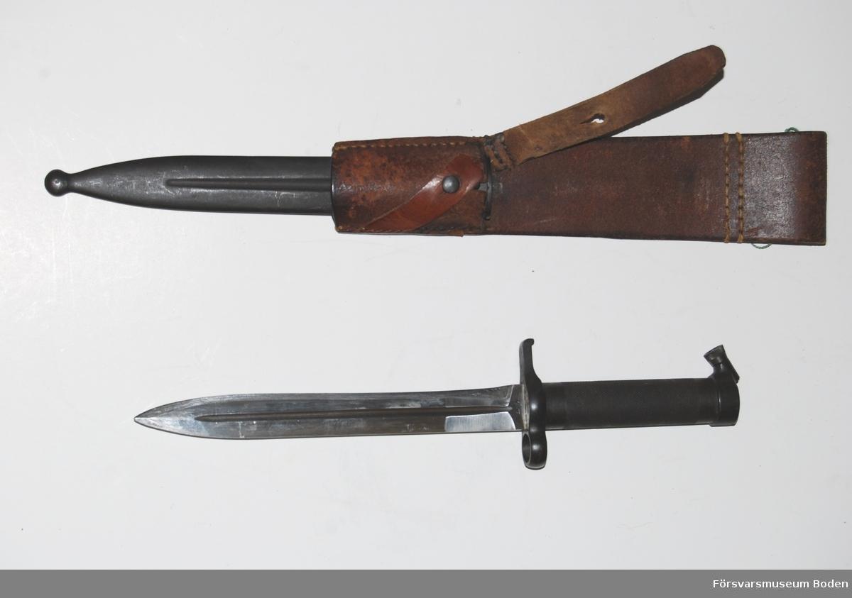 Kort knivbajonett med stålfäste och eneggad klinga avsedd för gevär m/1896. Konisk låsknapp. Med bäranordning av lång modell med två slejfar samt stålbalja. Bäranordningen har stämpel från Norrbottens regemente I 19, Boden.