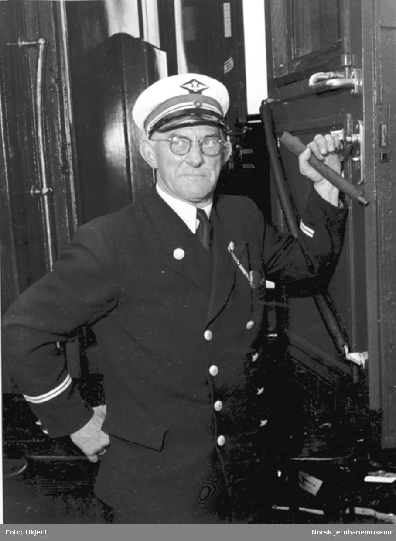 Overkonduktør Hans Kjosbakken i døra på en av vognene i åpningstoget for elektrisk drift til Hamar