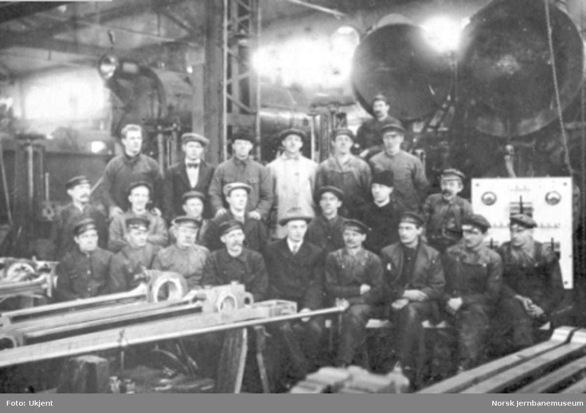 En gruppe verkstedarbeidere oppstilt for fotografering med damplokomotiver i bakgrunnen