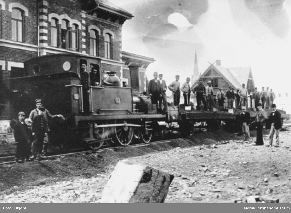 Lillehammer stasjon under anlegget; damplokomotiv type I nr. 13 med grusvogner og mannskap foran stasjonsbygningen