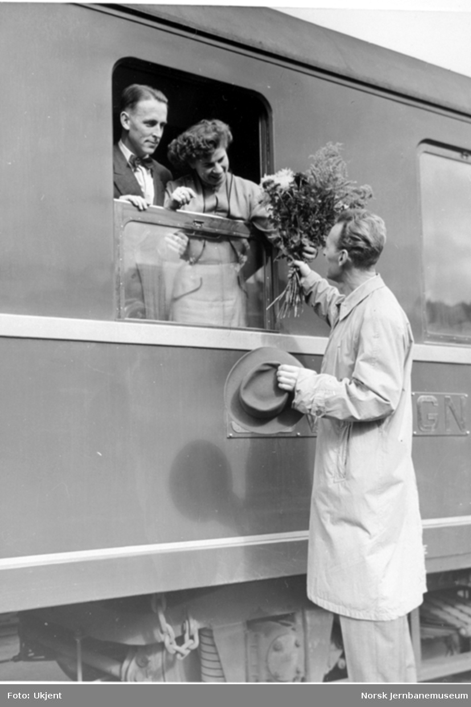 To reisende i en sovevogn får overrakt blomster gjennom vinduet