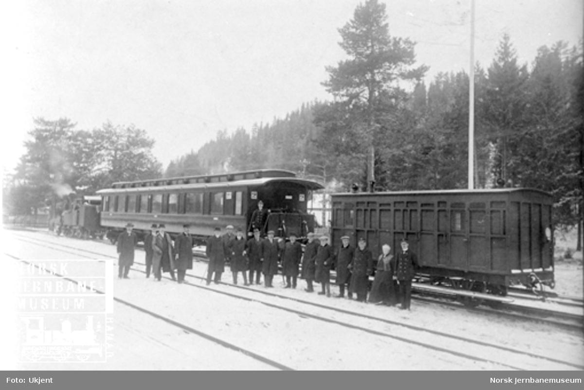 Åpningstoget for treskinnesporet Elverum-Rena, bestående av damplokomotiv type VII, en normalsporet personvogn og en smalsporet karet og deltakerne oppstilt for fotografering
