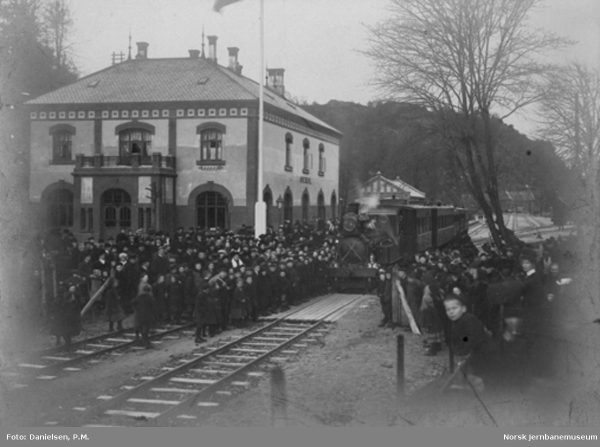 Åpningstoget ved returen til Arendal stasjon, trolig ved åpningen til Froland 23. november 1908 : stor folkemengde på stasjonen, hvor lokomotivstall og verksted er under bygging i bakgrunnen