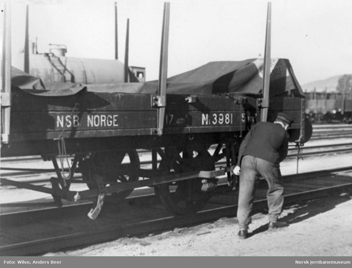 En jernbanemann legger på fallbrekket på stakevogn litra N1 nr. 3981