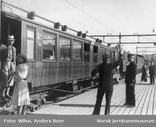 Plattformen på Østbanen med personvogn nr. 306 i tog som er klar til avgang; reisende og konduktør som gir avgangssignal