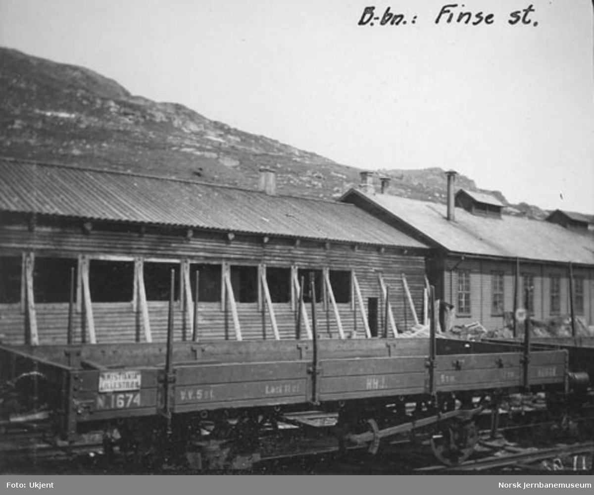 Stakevogn litra N nr. 1674 med snøoverbygg og lokomotivstallen på Finse i bakgrunnen