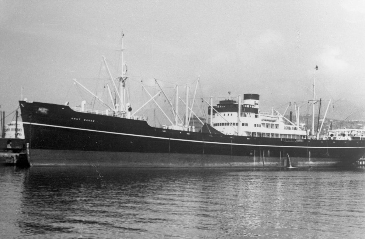 """Linjeskipet M/S """"Knut Bakke"""" ankret opp. To andre skip og land i bakgrunnen."""