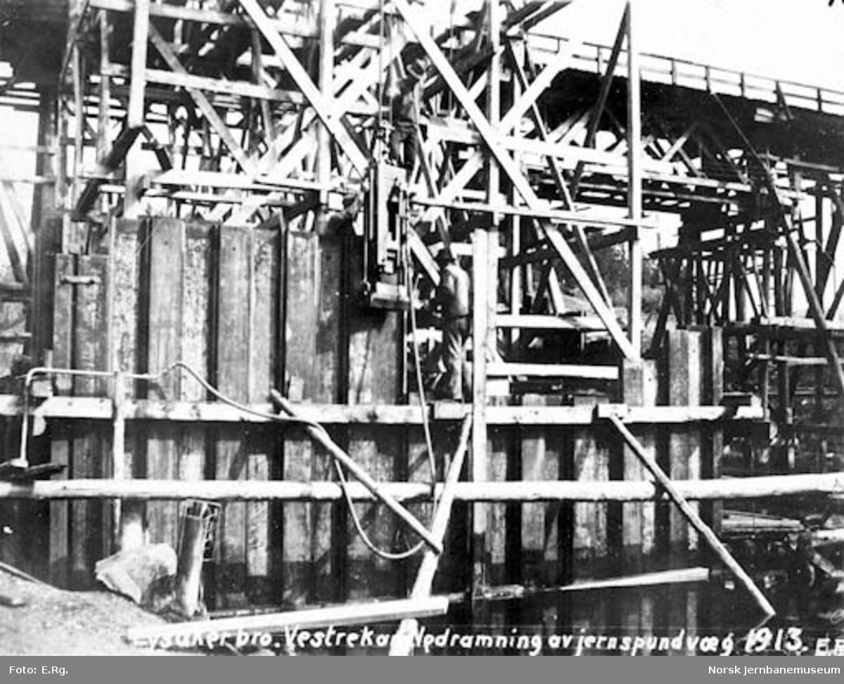 Drammenbanens omlegging : Lysakerelva bru, nedramming av jernspuntvegg ved vestre brukar