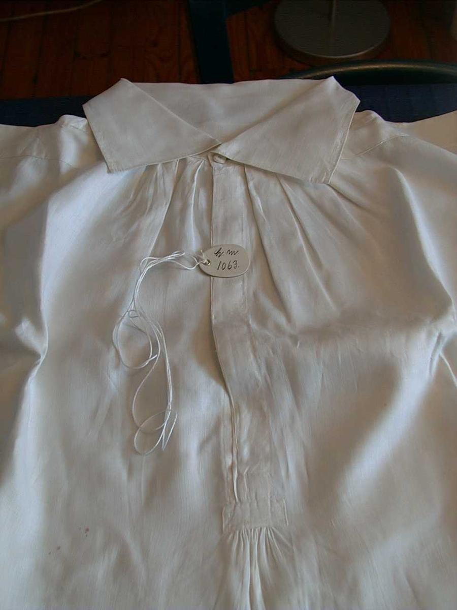 """Skjorte, hvit lin m/høy snipp, """"fadermordersnipp"""". Lukkes med en knapp i halsen. Vide ermer som er rynket ved skuldrene og til mansjettene. Smal mansjett som lukkes med en knapp. Knappene er trukket med tråd. Lange skjorteflak."""