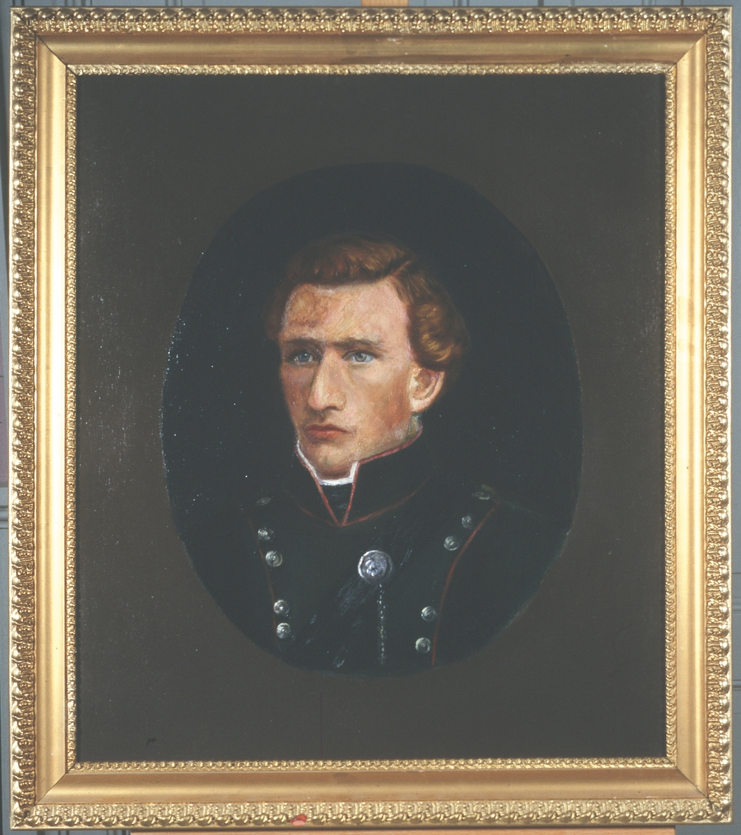 Portrett av eidsvollsmann Peter Johnsen Ertzgård Mann innskrevet i oval, på lysere bunn Brunt hår, uniform med smale, røde kanter, mange knapper.