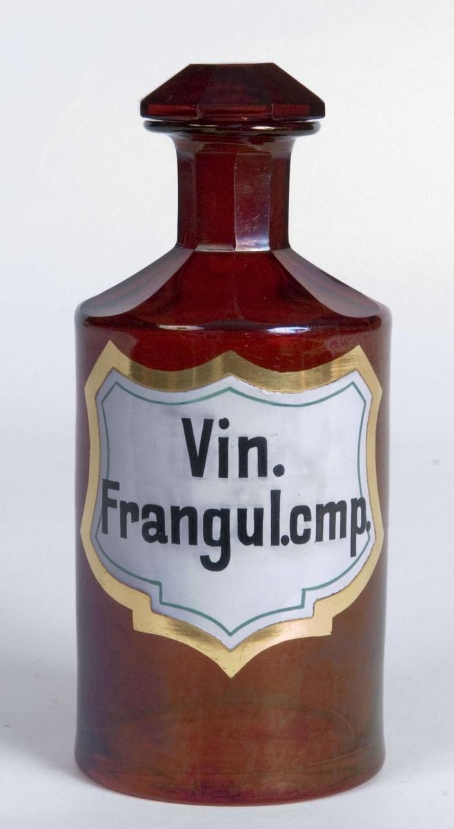 Standglass med propp. 9-kantet skulder og hals. 8-kantet propp. Skjoldformet etikett. Emaljefarget.