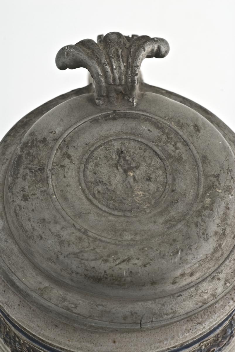 """Krus i grå keramikk av en type som stammer fra Westerwald-området i Tyskland. Karakteristisk er risset og stemplet dekor og pålagte relieffer, farget med koboltblått og senere også manganfiolett, under klar saltglasur. Dette lave, sylinderformete kruset kalles """"Humpen"""" og ble masseprodusert gjennom hele 1600 og 1700-tallet.  Krus med komplett lokk."""