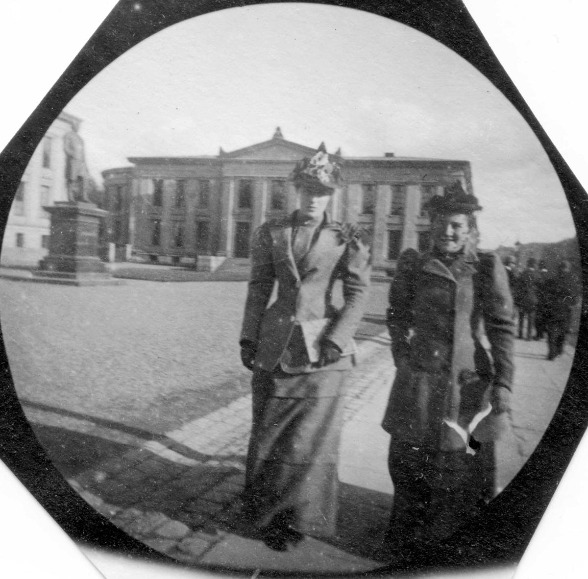 To damer spaserer langs Karl Johans gate, Oslo, ved Universitetsplassen.