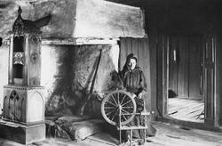 Kvinne sitter ved rokk foran grua i stua. Gevær inne i peise