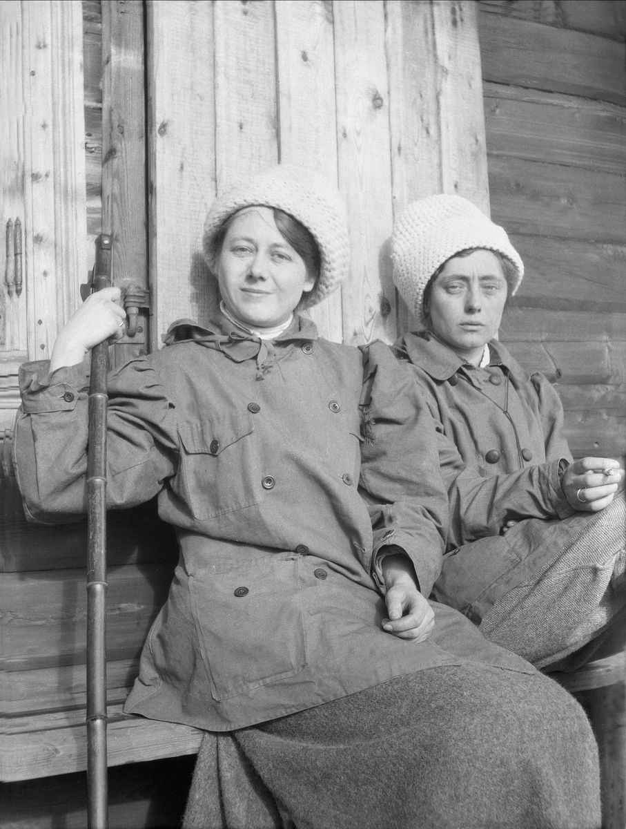 To kvinner sitter utenfor en husvegg. Robsahm og Lund.